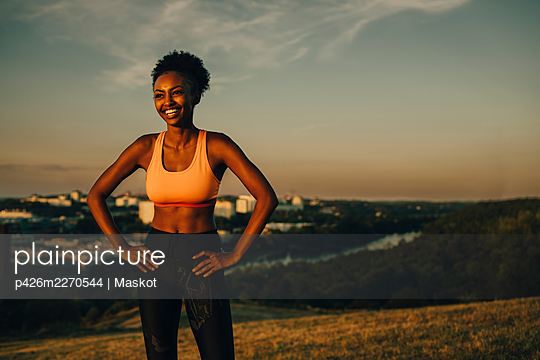 Smiling female athlete with hand on hip during sunset - p426m2270544 by Maskot