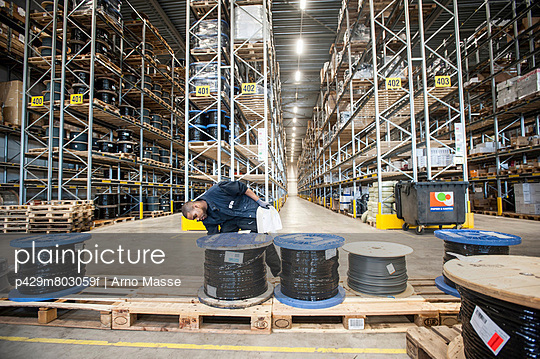Male warehouse worker checking pallet order - p429m803059f by Arno Masse