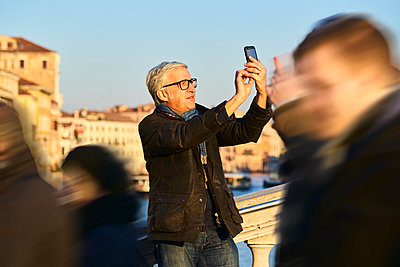 Man takes picture with the smartphone on a bridge - p1312m2082164 by Axel Killian