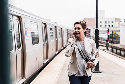 Mature woman using smart phone at commuter train station - p300m1192341 by Uwe Umstätter