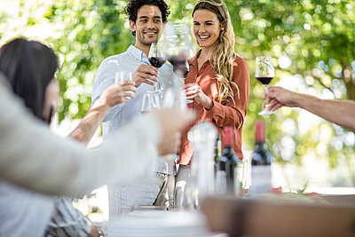 Couple raising a toast together with wine in garden - p300m1204801 by zerocreatives