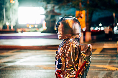 Spaceman on a street in the city at night attracted by shining projection screen - p300m2043183 von Vasily Pindyurin