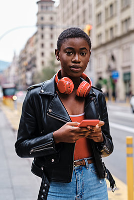 Woman wearing jacket and headphones using mobile phone while standing in city - p300m2250165 by Alvaro Gonzalez