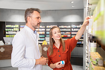 Female customer taking medicine from shelf while standing with male pharmacist in store - p300m2251839 by Florian Küttler