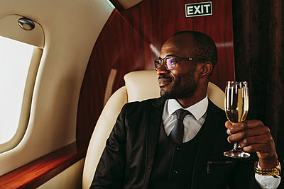 Smiling male entrepreneur holding champagne looking through window in private jet - p300m2257065 by OneInchPunch