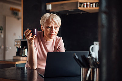 Smiling businesswoman looking at laptop while holding coffee cup at kitchen counter in home office - p300m2267826 by Robijn Page