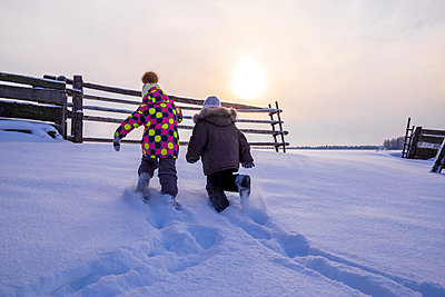 Boy and girl trudging through snow covered landscape, rear view - p429m2068943 by Aliyev Alexei Sergeevich