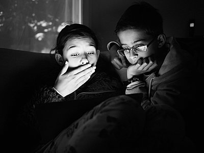Mixed race children using digital tablet at night - p555m1411859 by Donald Iain Smith