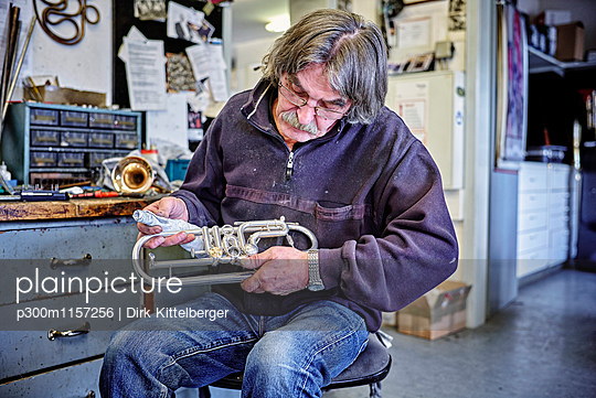 Instrument maker cleaning trumpet in workshop - p300m1157256 by Dirk Kittelberger
