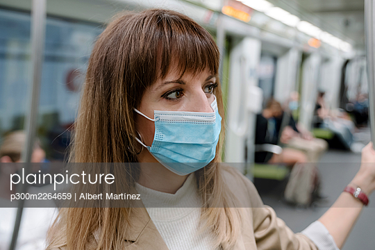 Woman with protective face mask looking away while traveling by subway train during pandemic - p300m2264659 by Albert Martínez