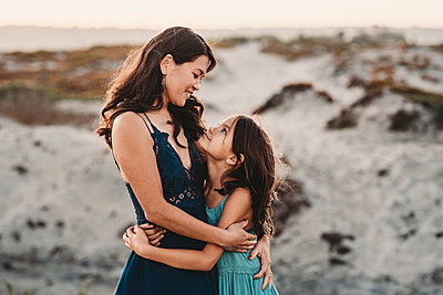 Happy mother hugging 8 yr old daughter at the beach - p1166m2207853 by Cavan Images