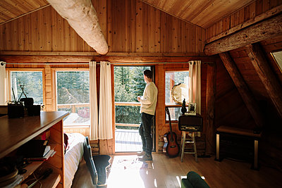 Serene man drinking coffee at sunny cabin doorway - p1192m2094213 by Hero Images