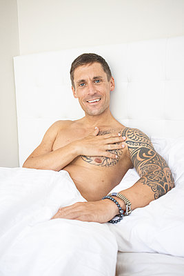 Man with tattoos in the bed, portrait - p1640m2259604 by Holly & John