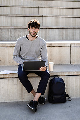 Man sitting on outdoor stairs using laptop - p300m2140412 by Giorgio Fochesato