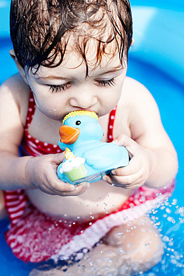 Young Girl Sitting in Pool With Rubber Duck - p694m663676 by Maria K