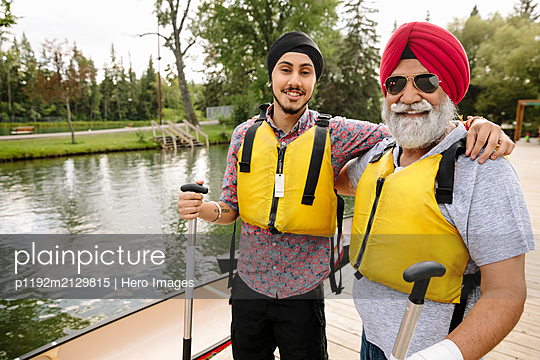 Portrait of mature Indian man and son wearing life jackets - p1192m2129815 by Hero Images