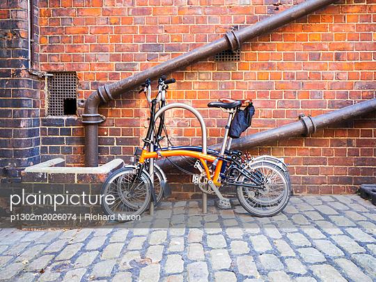 Zwei klappbare Fahrräder der Marke Brompton an einer Backsteinmauer - p1302m2026074 von Richard Nixon