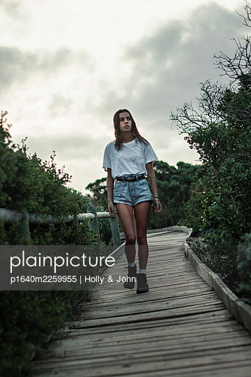 Young girl on wooden boardwalk - p1640m2259955 by Holly & John