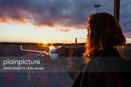 Young woman looking through window on plane at the airport at sunset - p300m2042219 von Kike Arnaiz