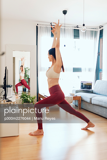 Mature woman practicing yoga while looking in mirror at home - p300m2276044 by Manu Reyes