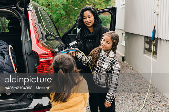 Woman guiding daughter in charging electric car while going for picnic - p426m2194962 by Maskot