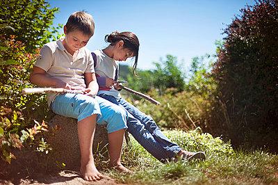 Boy and girl cutting wood sticks 1 - p1007m854307 by Tilby Vattard