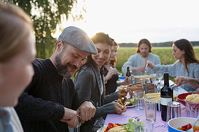 Friends enjoying summer garden party in rural summer yard - p1192m1490389 by Hero Images
