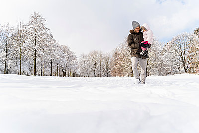 Father carrying daughter walking in winter landscape - p300m2083156 by Daniel Ingold
