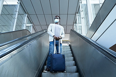 Businessman wearing protective face mask holding luggage while standing on escalator at station - p300m2241544 by Pete Muller