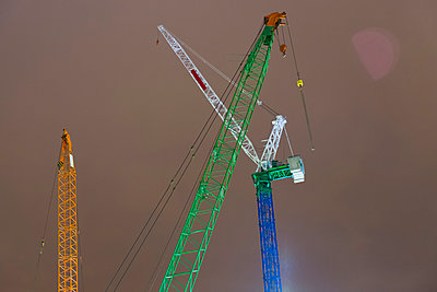 Low angle view of construction cranes against sky - p301m1406544 by Michael Mann