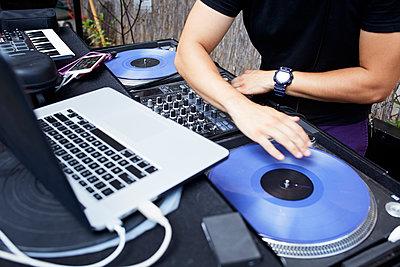 Hispanic dj playing music in backyard - p555m1303255 by Granger Wootz