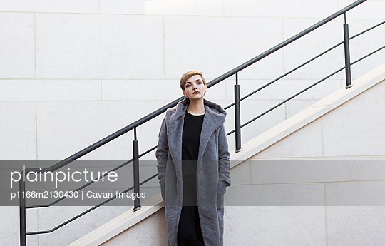 woman with short tousled hair in gray coat on stairs background - p1166m2130430 by Cavan Images