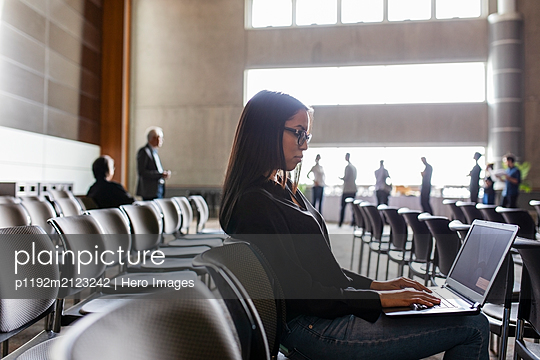 Businesswoman working at laptop in conference audience - p1192m2123242 by Hero Images