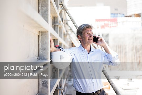 Man on cell phone on construction site - p300m2004242 von Robijn Page