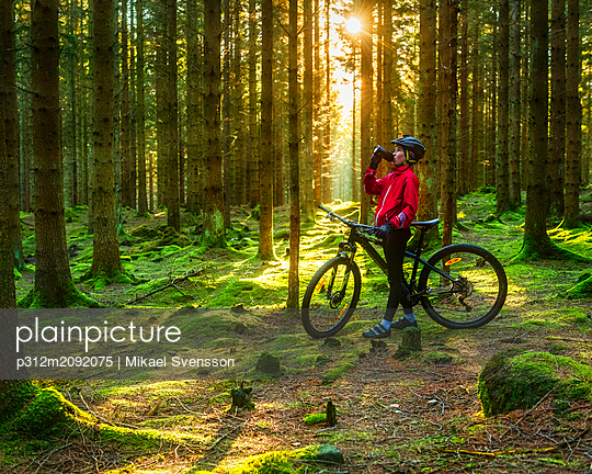 Cyclist in forest - p312m2092075 by Mikael Svensson