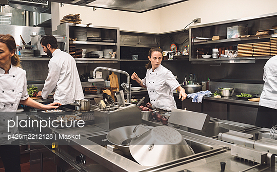 Chefs working in commercial kitchen at restaurant - p426m2212128 by Maskot