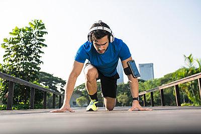 Runner training start position on street in urban park, wearing headphones - p300m1550272 by Steve Brookland