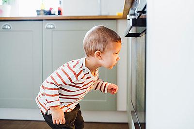 Toddler boy looking at oven in kitchen at home - p300m2080357 von HalfPoint