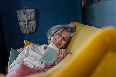 Senior woman smiling while reading book at home - p300m2265905 by Emma Innocenti