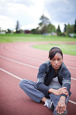 Young female sprinter stretching at track - p4342609f by Alin Dragulin