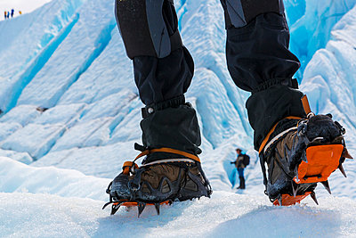 View of a hiker's feet wearing crampons with the face of the Matanuska Glacier and a second hiker in the background, Southcentral Alaska, Summer, USA. - p442m999846 by Lynn Wegener