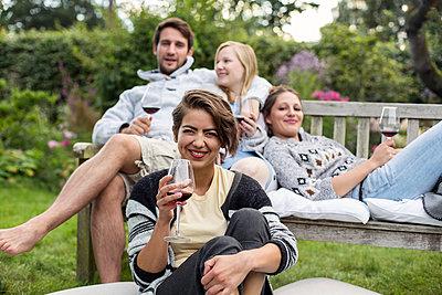Freunde im Garten genießen Rotwein - p788m1165265 von Lisa Krechting