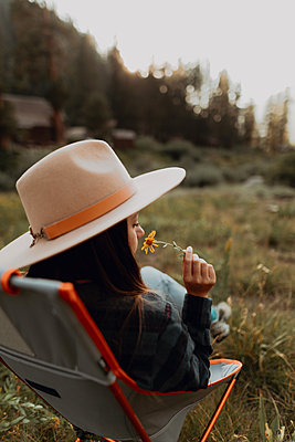 Young woman in stetson smelling wildflower on deck chair in rural valley, rear view, Mineral King, California, USA - p924m2127233 by Peter Amend