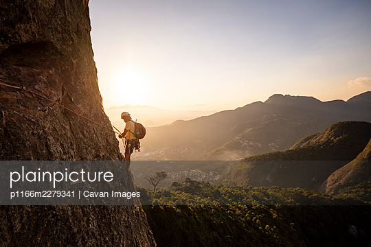 Beautiful view to male climber on steep rocky rainforest mountain - p1166m2279341 by Cavan Images