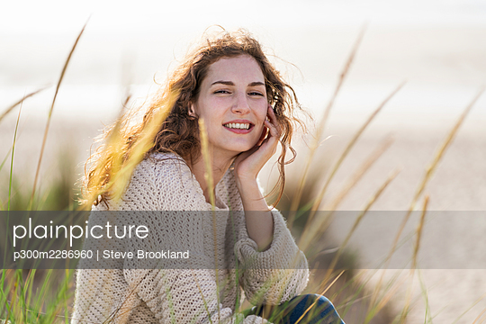 Smiling young woman with hand on chin sitting in dunes at beach - p300m2286960 by Steve Brookland