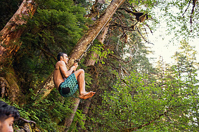 Low angle view of man swinging on rope in forest - p1166m1423040 by Cavan Images