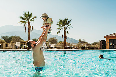 Father throwing young boy up in air while playing in pool on vacation - p1166m2218178 by Cavan Images