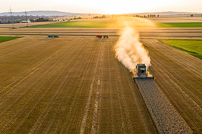 Aerial view of combine harvester on agricultural field against sky during sunset - p300m2143579 by Martin Moxter