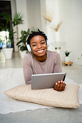 Smiling female entrepreneur using digital tablet at home - p300m2256524 by Rafa Cortés