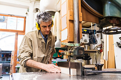 Mature male craftsperson wearing ear protectors while working in workshop - p300m2293665 by Eugenio Marongiu